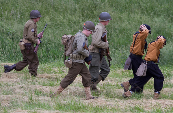 At a World War II Reenactment, as part of the Sigel Sesquicentennial celebration, American soldiers take two German soldiers as prisoners of war.