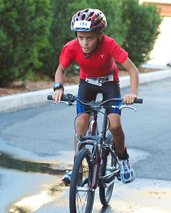 072212, Cambridge, MA -  Nyle Linnard, 8, of Weston, picks up speed during the three mile bike ride portion of the inaugural New England Kids Triathlon at M.I.T.'s Johnson Athletic Center. Herald photo by Ryan Hutton