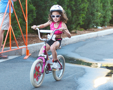 072212, Cambridge, MA -  Shelley Johnston, 8, of Weston, cruises along during the three mile bike ride portion of the inaugural New England Kids Triathlon at M.I.T.'s Johnson Athletic Center. Herald photo by Ryan Hutton