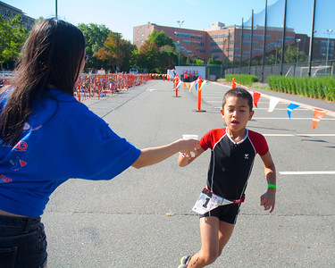 072212, Cambridge, MA -  Cyrus Tavakol, 8, of Concord grabs some water during the half mile run portion of the inaugural New England Kids Triathlon at M.I.T.'s Johnson Athletic Center. Herald photo by Ryan Hutton