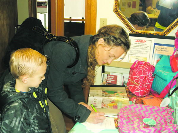 Heather Stovall of Toledo signs up for a raffle at the annual Spring Market Fundraiser in Toledo, as son Gavin looks on. A number of vendors displayed their wares at the center. Proceeds from the market go to fund Life Center activities for seniors in Cumberland and Clark counties.