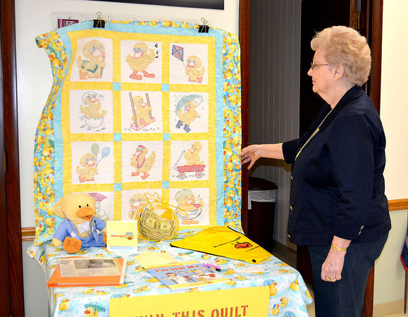 Nita Motogawa, a board member of the Effingham Home Extension group, looks at a quilt she and other board members to raise money for Chemo Ducks, toys given to children with cancer. The quilt was on display Saturday at the Home Extension Quilt Show in Effingham. The unit was able to buy 17 ducks with money raised from last year's quilt.