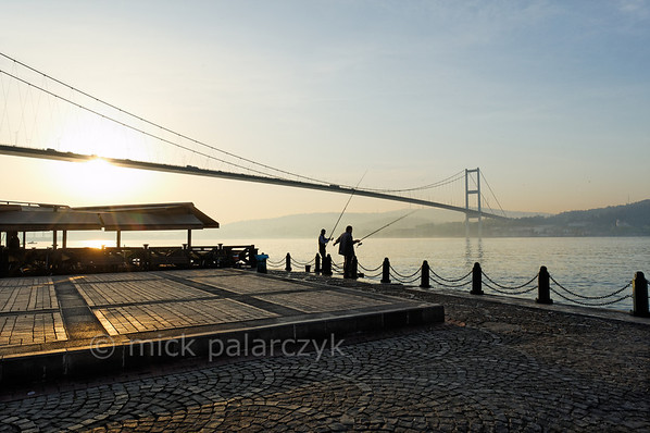 [TURKEY.ISTANBUL 29129 'Bosphorus Bridge at Istanbul.'  	Fishermen enjoy the rising sun on the quay of the Bosphorus in Ortaköy, a city district of Istanbul. The nearby Bosphorus Bridge connects the European part of Turkey to the Asian part (on the right). Photo Mick Palarczyk.