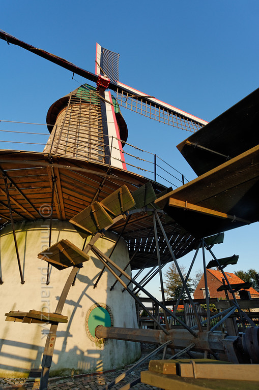"""[HOLLAND.NOORDBRABANT 29316] 'Wind and water powered mill in Dinther.'  The """"Kilsdonkse Molen"""" near the village of Dinther is a rare combination of a wind and water powered mill. The mill was first mentioned in the 15th century as a wooden watermill on the bank of the Brabantse Aa. The present brick buildings date from 1842 and were restored in 2008. The corn grinding machinery in the tower mill on the right bank of the brook is powered by wind as well as by a waterwheel which is attached to the conical tower. The Dutch term for such a mill is """"watervluchtmolen"""". A second waterwheel (the blades of which are visible on the right) drives an oil mill which is housed in a building on the left bank of the brook. Photo Mick Palarczyk."""