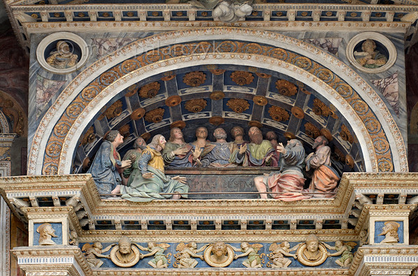 [ITALY.VALLEDAOSTA 28490 'The Assumption of Mary.'  	The façade of Aosta's cathedral boasts an early 16th century terra cotta group of apostles gathered around the tomb of Mary. They look up in awe as she (invisible in this scene) ascends to heaven. Photo Mick Palarczyk.