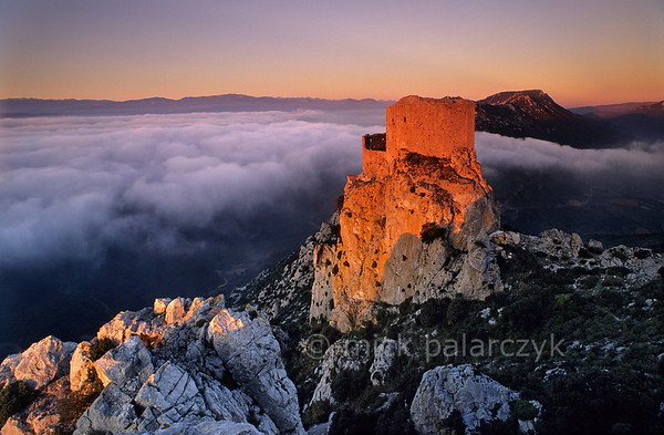 [FRANCE.LANGUEROUS 28319] 'Château de Quéribus.'  The medieval Château de Quéribus, sitting atop the Corbières mountain range, catches the first rays of the sun, while the neighbouring valley is covered with clouds. It is one of the last strongholds where followers of the Cathar religion could find refuge during their persecution in the first half of the 13th century. The castle is located 25 km northwest of Perpignan. Photo Mick Palarczyk.