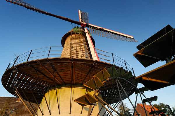 """[HOLLAND.NOORDBRABANT 29318] 'Wind and water powered mill in Dinther.'  The """"Kilsdonkse Molen"""" near the village of Dinther is a rare combination of a wind and water powered mill. The mill was first mentioned in the 15th century as a wooden watermill on the bank of the Brabantse Aa. The present brick buildings date from 1842 and were restored in 2008. The corn grinding machinery in the tower mill on the right bank of the brook is powered by wind as well as by a waterwheel which is attached to the conical tower. The Dutch term for such a mill is """"watervluchtmolen"""". A second waterwheel (the blades of which are visible on the right) drives an oil mill which is housed in a building on the left bank of the brook. Photo Mick Palarczyk."""