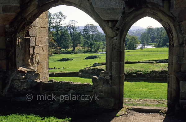 [BRITAIN.ENGNORTH 22996] 'Bolton Abbey.'  	The River Wharfe and its green valley seen from the church choir at Bolton Abbey in North Yorkshire. The Augustinian priory was founded in 1152. Building work was still going on at the abbey when the Dissolution of the Monasteries (ordered by Henry VIII) resulted in the termination of the priory. Photo Mick Palarczyk.