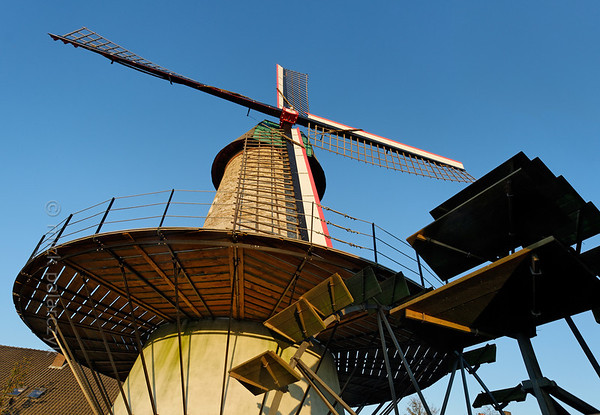 """[HOLLAND.NOORDBRABANT 29317] 'Wind and water powered mill in Dinther.'  The """"Kilsdonkse Molen"""" near the village of Dinther is a rare combination of a wind and water powered mill. The mill was first mentioned in the 15th century as a wooden watermill on the bank of the Brabantse Aa. The present brick buildings date from 1842 and were restored in 2008. The corn grinding machinery in the tower mill on the right bank of the brook is powered by wind as well as by a waterwheel which is attached to the conical tower. The Dutch term for such a mill is """"watervluchtmolen"""". A second waterwheel (the blades of which are visible on the right) drives an oil mill which is housed in a building on the left bank of the brook. Photo Mick Palarczyk."""