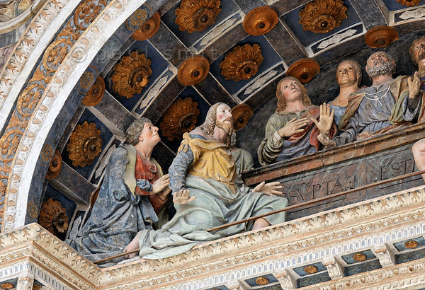 [ITALY.VALLEDAOSTA 28492 'The Assumption of Mary.'  	The façade of Aosta's cathedral boasts an early 16th century polychrome terra-cotta group of apostles gathered around the tomb of Mary. They look up in awe as she (invisible in this scene) ascends to heaven. Photo Paul Smit.