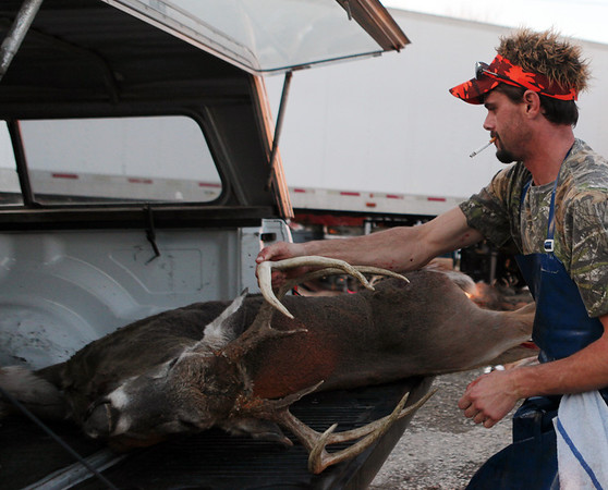 Ray Bowen unloads a buck at Mike's Food Market in Louisville. Friday was the first day of shotgun season in Illinois, and Bowen said they received around 60 deer for processing Friday morning.