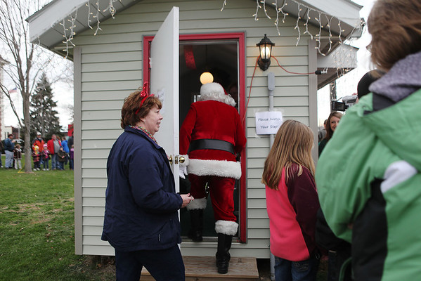 Santa climbs into his house to greet children Saturday during Old Fashioned Christmas in Effingham.