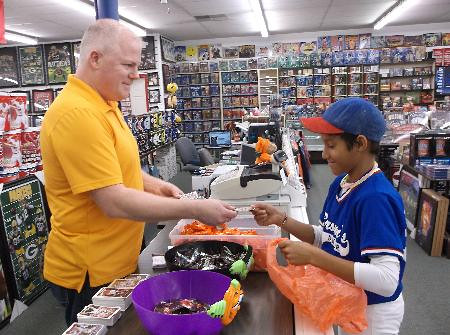 Trick-or-treating through downtown Effingham in his baseball gear, Jett McMillan of Effingham chose a baseball card over candy from John Schafer, owner of the Baseball Card Connection.