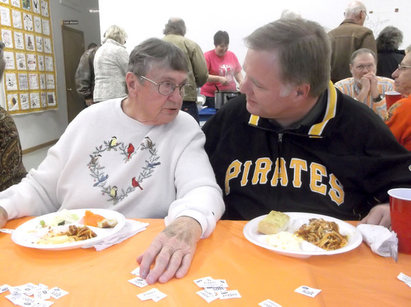 Ina Abendroth and Paul Black visit during a spaghetti supper benefit at St. Elmo Christian Church. Abendroth was one of several people left homeless by severe storms in November. Black is the director of communications for the Illinois Great Rivers Conference of the United Methodist Church.
