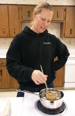 Prior to making lip balm out of homegrown beeswax and honey, Michelle Barnick heated up the products at the University of Illinois Extension Center in Effingham.