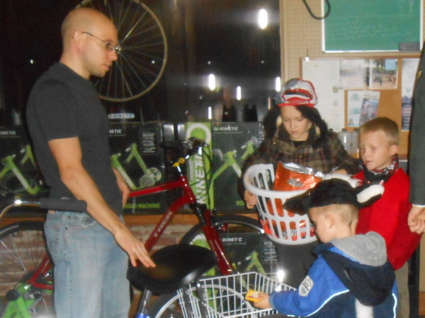 Robby Sans hands out candy to Lucy Fearday, 8, Will Fearday, 6, and Mike Fearday, 4, of Effingham at Bike & Hike. Downtown businesses opened their doors on Halloween to trick-or-treaters.