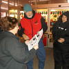Kmart employee Joann Ross hands out tickets for shoppers Bob Orsborn, center, and Rachel Poland. The tickets enabled shoppers to come back later in the day for their desired items.