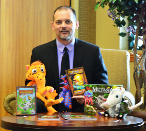 Effingham teacher Joe Fatheree is surrounded a variety of items from the production company Mutasia, which he will debut at Helen Matthes Library's Family Read Night at the Effingham Performace Center Thursday.