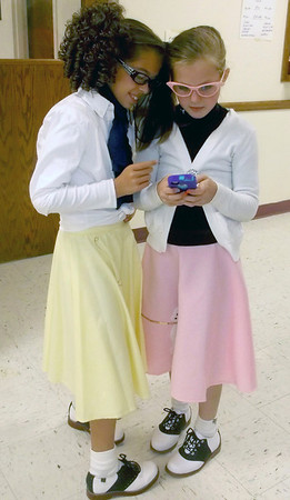 Isabellla Kronewitter, left, and McKenzie Wittenberg, both fifth-graders at Central School in Effingham, show how old school can meet new school at the annual Stewardson Costume Contest and Raffle at the Stewardson Community Building. The girls are modeling 1950s attire while playing an electronic game. McKenzie's dad Rick grew up in Stewardson. The event was sponsored by Stewardson American Legion Post 611.