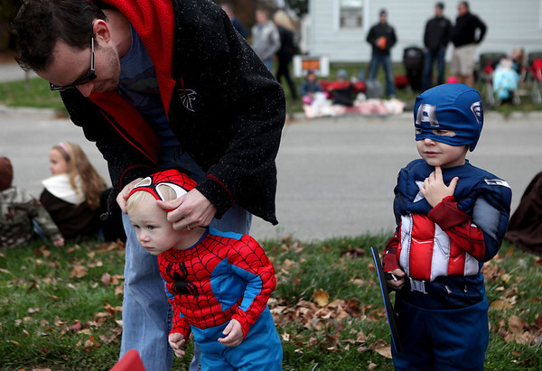 Brian Bannister, of Effingham, helps his son Lyndon with his mask during the Halloween Parade as brother Calvin looks on.