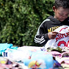 Manaya Mossman of Teutopolis picks up a Chris Carpenter jersey at a yard sale on Kreke Street during Effingham's citywide garage sale.