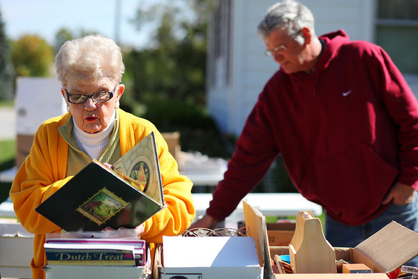 "Adele Krueger flips through a copy of ""Puss in Boots"" at a yard sale on Temple Avenue in Effingham. The weekend marked citywide garage sales, but Joyce Kaufman said the weather may have affected sales at her house. ""Usually I do really well, but I think it was just too cold,"" she said."
