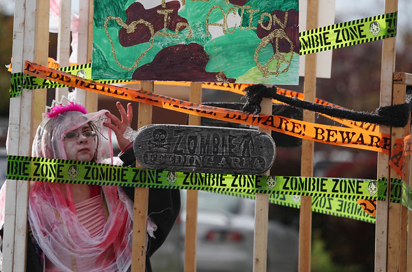 A girl dressed as a zombie peers off of her float during the Halloween Parade.