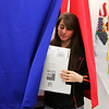 """Abby Poe, of Effingham, steps out of a voting booth at the County Clerk's office. Louise Johnson, deputee clerk, said that more that 1,460 ballots have already been cast, a higher number than last year's. """"Every presidential election seems to get a little larger than the last one,"""" she said."""