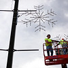 "City of Effingham employees Darren Moomaw, left, and Todd Lohmann hang snowflakes on the corner of Fourth Street and Washington Avenue. ""We're trying to get them up before winter,"" Moomaw said."