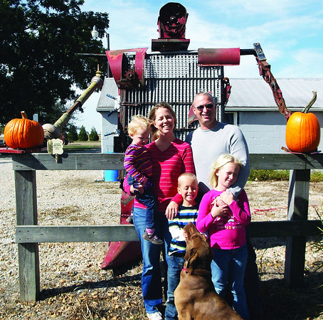 Heath McCormick built a large robot that stands in his yard just off Route 32 south of Stewardson. Heath is pictured with his wife, Autumn, and three kids (pictured from left) Lorelei, 2, Ross, 5, and Claire, 8. Also in the photo is the family dog Zeba.