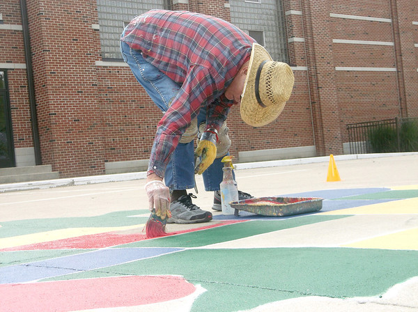 Gene Alexander paints Kansas in red during a project at St. Anthony Grade School this week. Alexander has painted more than 200 United States maps on playgrounds throughout the southern half of the state.