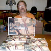 With a stack of books in front of him at his Effingham home, local author Kyle Packer shows an enlarged version of the cover of a book he authored.