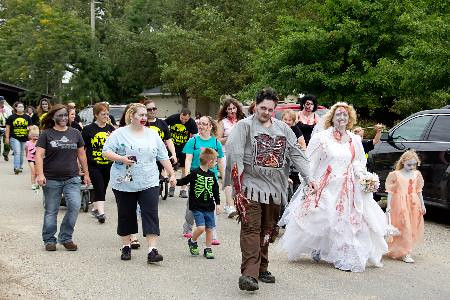 A pack of zombies walks through Evergreen Park, raising money and awareness for the American Cancer Society.