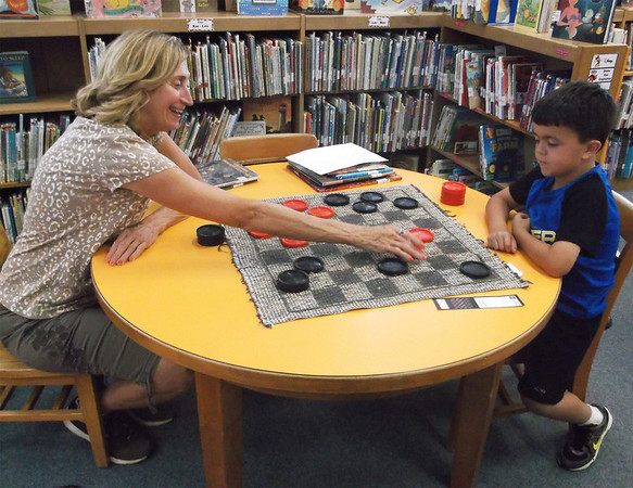 Debbie Kull and her grandson Desmond Klimpel, both of Altamont, celebrated National Checkers Day by playing on one of the many boards set up around the Helen Matthes Library Monday afternoon.