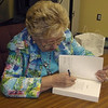 "Joanne Hardy signed copies of her novel ""The Girl in the Butternut Dress"" at the Helen Matthes Library recently."