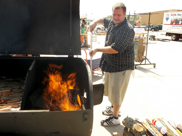 Devin Radloff of Strasburg stokes the fire for burgers and dogs to be served at Freedom Fest behind Village Square Mall in Effingham recently. The event, which also featured a food giveaway, was sponsored by Enduring Freedom Ministries.