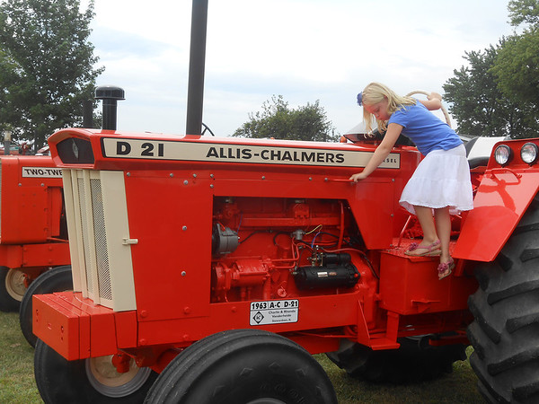 Emma Deters of Sigel climbs off a tractor at Cap & Bud's 10th Annual Good Ol' Boys Tractor Show in Shumway Sunday. Nearly 150 tractors were on display at the show this year.