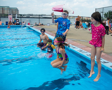 071612, Boston, MA - From left, Thomas Garity, Chase Rubin, Vinnie O'Byrne, Natalie Rubin and Victoria Garity jump into the North End's Mirabella Pool to stay cool on Monday. Herald photo by Ryan Hutton