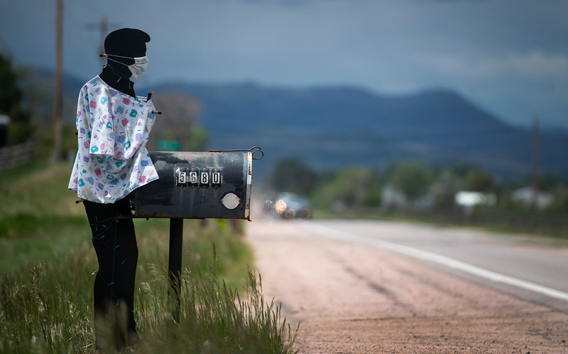 A cutout of a man along Colorado Highway 1 wears a mask and medical shirt as the coronavirus pandemic continues near Wellington, Colo. on Wednesday, May 27, 2020.