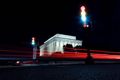 Traffic passes Lincoln Memorial at night