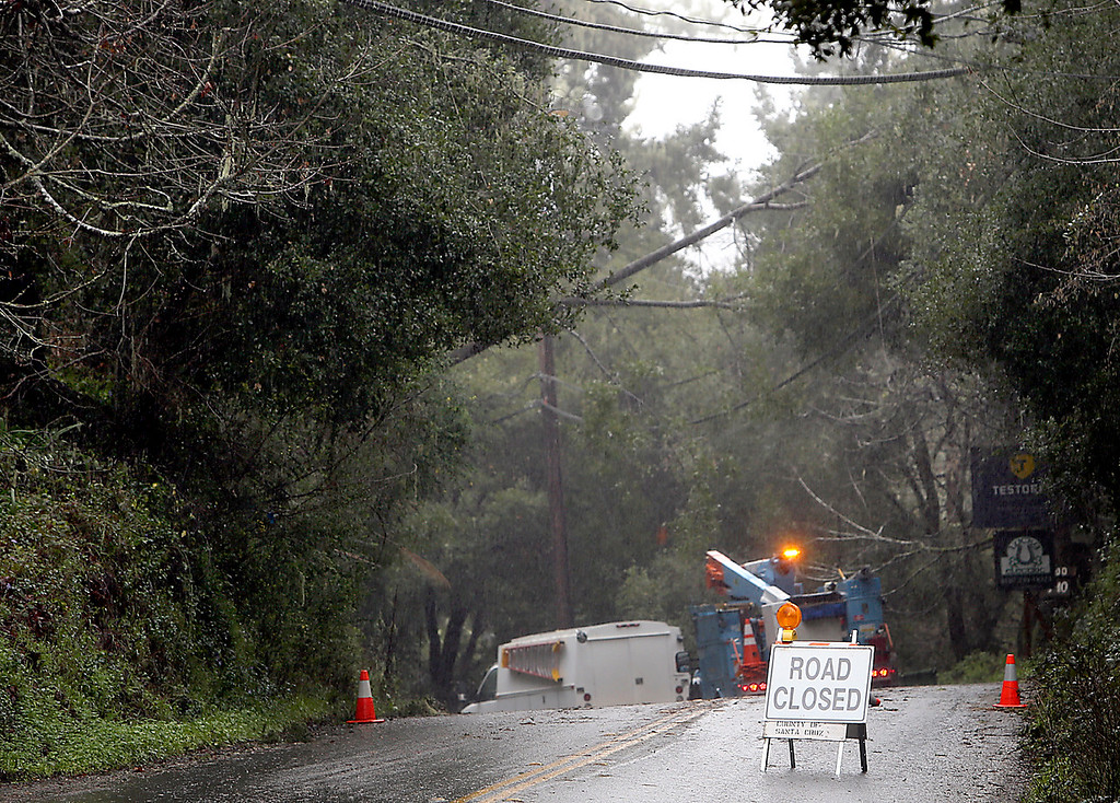 . PG&E crews work to clear downed power lines on Valencia Road in Aptos on Friday, where road closures forced Valencia Elementary to close. (Kevin Johnson -- Santa Cruz Sentinel)