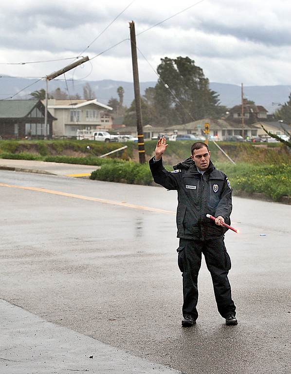 . Santa Cruz Police officer Raul Pizano diverts West Cliff Drive traffic at Almar Avenue Friday morning when  high winds snapped a utility pole and downed a large cypress tree.  (Dan Coyro -- Santa Cruz Sentinel)