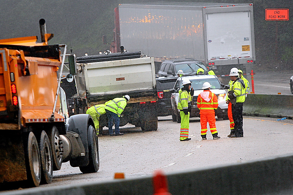 . Workers look beneath a dump truck that struck and killed one Graniterock worker and injured another at the emergency mudslide work site on Highway 17 just north of Scotts Valley Thursday morning.  (Dan Coyro -- Santa Cruz Sentinel)