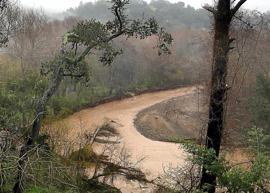 . A muddied and rain-swollen Soquel Creek flows along Old San Jose Road Thursday. (Shmuel Thaler -- Santa Cruz Sentinel)