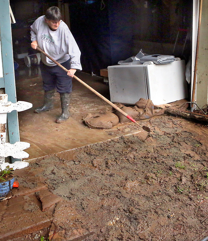 . Joanne Morisoli pushes mud out of her Felton garage on Wednesday as she and her partner Rose Morisoli clean up after Tuesday\'s flooding. (Shmuel Thaler -- Santa Cruz Sentinel)