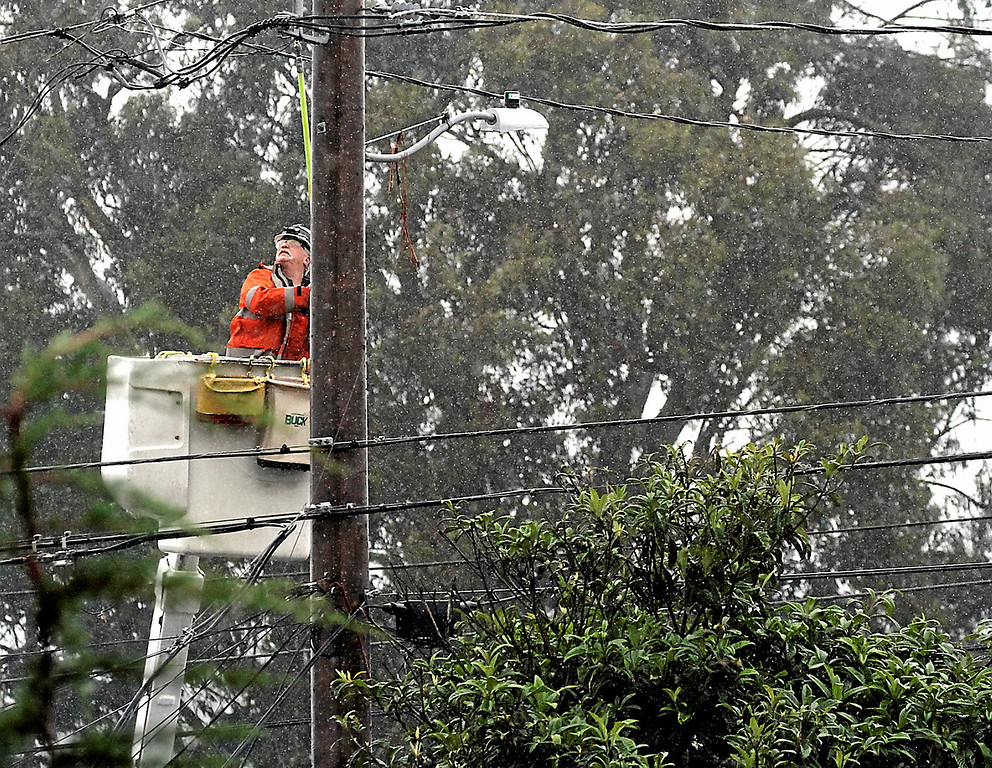 . A PG&E worker responds to downed wires near East Cliff Drive Thursday afternoon. (Shmuel Thaler -- Santa Cruz Sentinel)