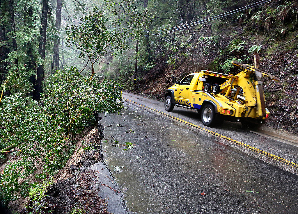 . A tow truck drives past a slipout on Lompico Road Wednesday. (Shmuel Thaler -- Santa Cruz Sentinel)