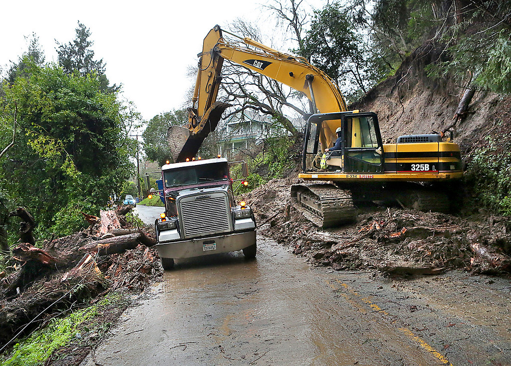 . A crew works to clear a mudslide on Cherryvale Avenue in Soquel Wednesday morning. (Shmuel Thaler -- Santa Cruz Sentinel)