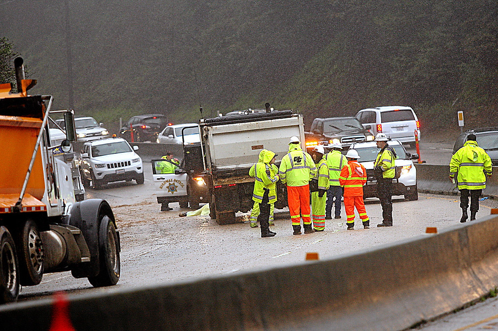 . A Graniterock contract worker at the Highway 17 mudslide worksite was killed Thursday and another injured when a dump truck, pictured at center, struck both workers on the jobsite.  (Dan Coyro -- Santa Cruz Sentinel)