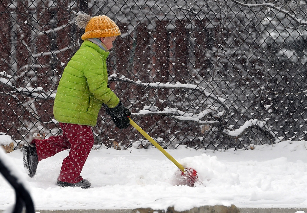 . Jackson Siefer, 5, makes shoveling snow a fun game at  Mapleton School during a February 10th snow in Boulder. Cliff Grassmick  Photographer  February 10, 2018